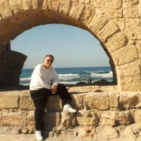 Ron in front of an aqueduct beside the Mediterranean Sea in the Holy Land